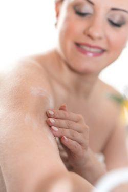 Portrait of smiling young woman applying moisturizing cream on her arm